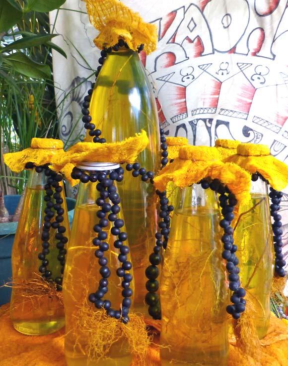 Des flacons de Monoi traditionnels décorés, l'huile macère avec des racines de Veti (vétiver)