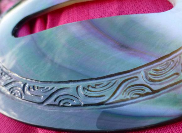 Les reflets irisés de la boucle de Pareo en nacre en font un objet aussi utile qu'élégant