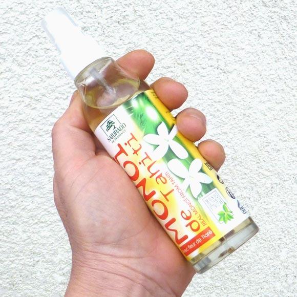 Flacon en verre imposant dans la main et muni d'un spray..